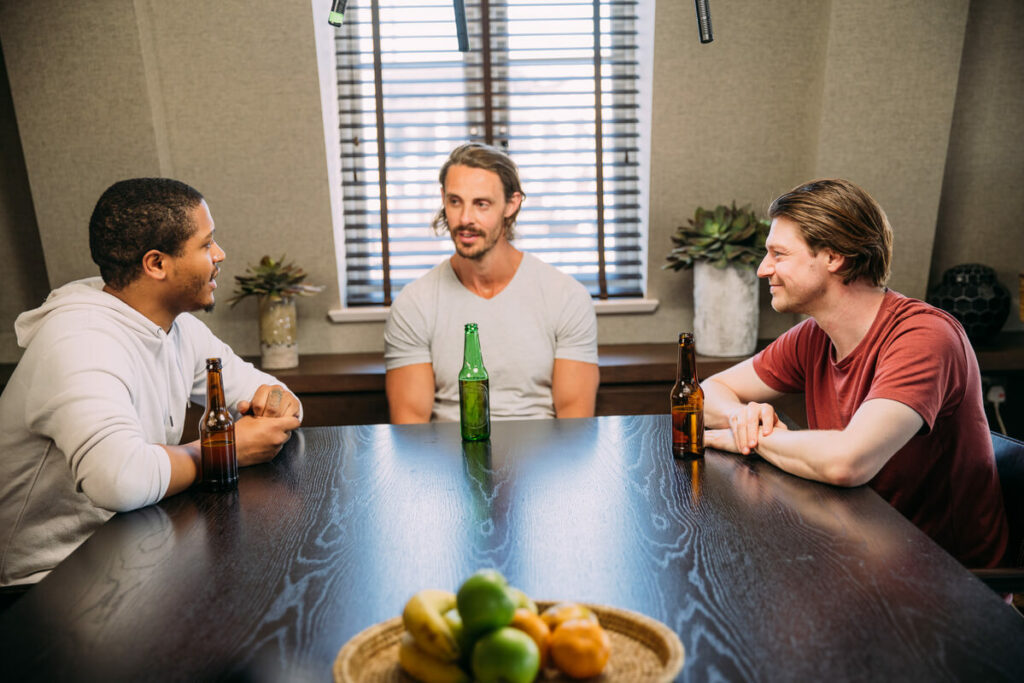 Three young guys sit at a table drinking beers.