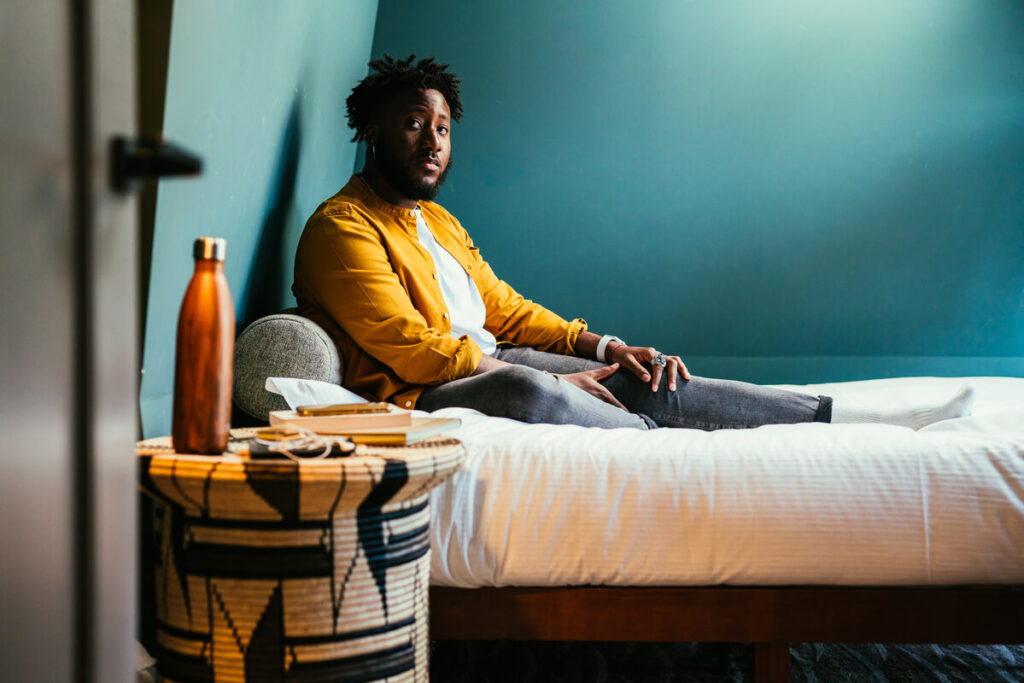 Young guy wearing a yellow shirt sits on his bed looking worried.